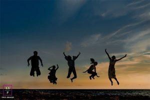 famille sautant de joie sur la plage à la blue hour