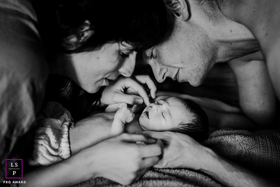 parents entourant leur nouveau-né de quelques jours lors d'une séance photo à domicile