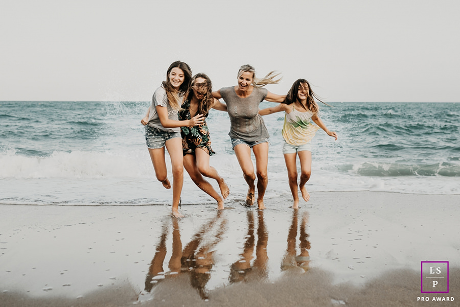 mother and daughters having fun at the beach